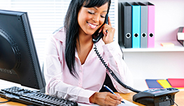 Smiling young black business woman on phone taking notes in office